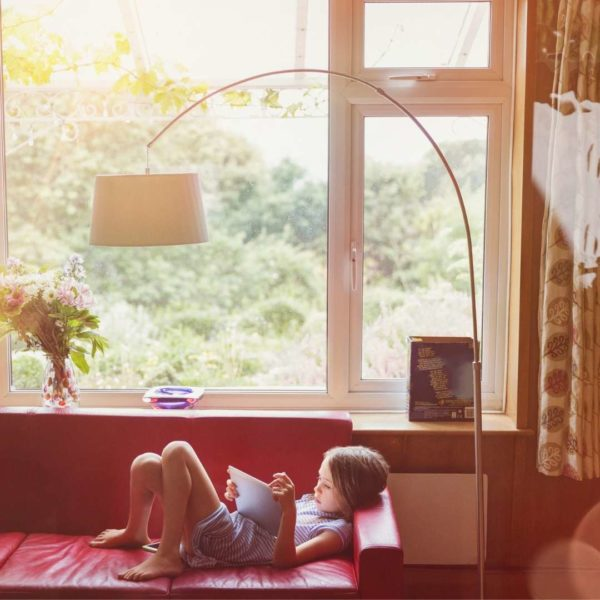 Best books for boys - boy reading on couch.